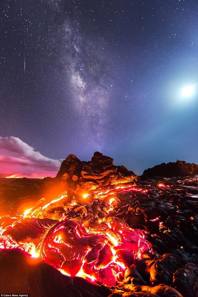 Khoảnh khắc hiện đang gây sửng sốt của tay máy người Mỹ Mike Mezeul. Trong bức ảnh này không chỉ có dòng nham thạch nóng đỏ mà còn có mặt trăng (góc phải), dải ngân hà (ở giữa) và một ngôi sao băng (sọc trắng mảnh ở góc trái).