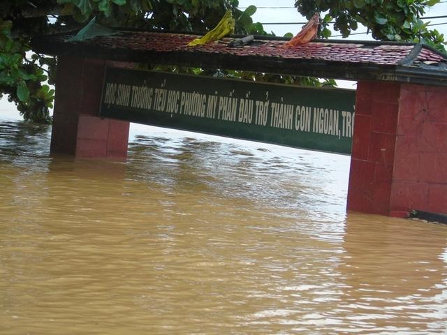 Nước lũ ngập gần lút cổng trường, không còn thấy bờ tường bao đâu.
