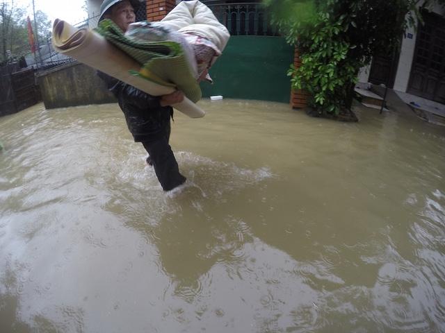 Nhiều hộ nước ngập nhà phải mang đồ sang hàng xóm xin ở nhờ.