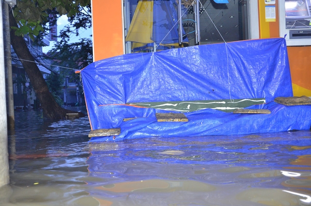 Nhà dân dắp đê, dùng bạt che chắn để không bị nước tràn vào nhà
