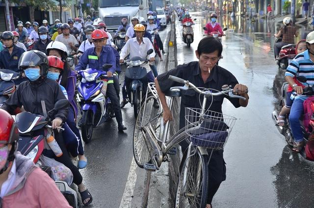 Người đàn ông vác xe đạp qua dải phân cách để thoát khỏi kẹt xe