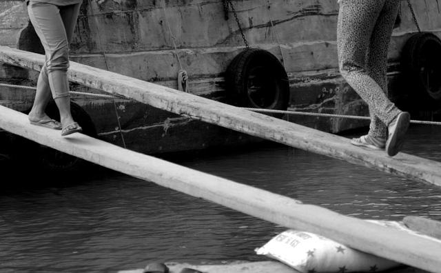 Cõng trên mình bao phân 50 kg, vượt qua những tấm ván nhỏ chỉ vừa đủ bàn chân nên khá nguy hiểm. Nhiều người lúc đầu làm chưa quen, cứ đi một quãng lại té nhào xuống dòng kênh.