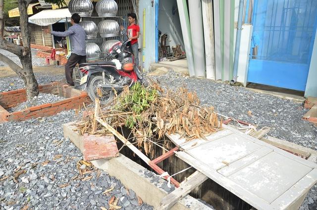 Một hố sâu trước cửa nhà dân được che đậy tạm bợ