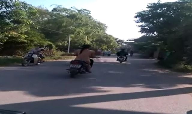 Cô gái khỏa thân đi xe máy trên đường đông người qua lại. Ảnh cắt từ video