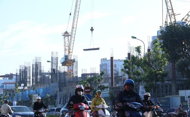 Các dự án xây dựng chung cư, nhà thương mại cao tầng liên tục mọc lên hai bên tuyến đường Lê Văn Lương - Tố Hữu - Lê Trọng Tấn. Cần cẩu sắt lơ lửng trên đầu người tham gia giao thông.