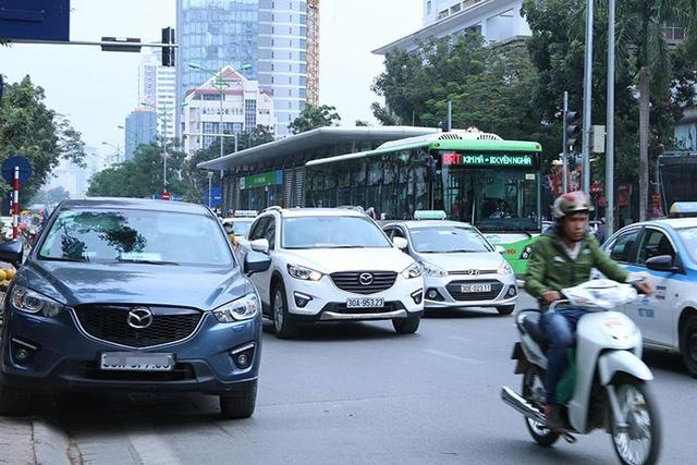 Chiếc ô tô đỗ gần như đối diện với nhà chờ xe buýt nhanh, dễ dàng nhận thấy việc đỗ xe như trên cản trở giao thông thế nào. Xe máy không có đường để đi, buộc phải đi sang làn đường bên cạnh trong khi rất nhiều ô tô cũng đang đi qua.