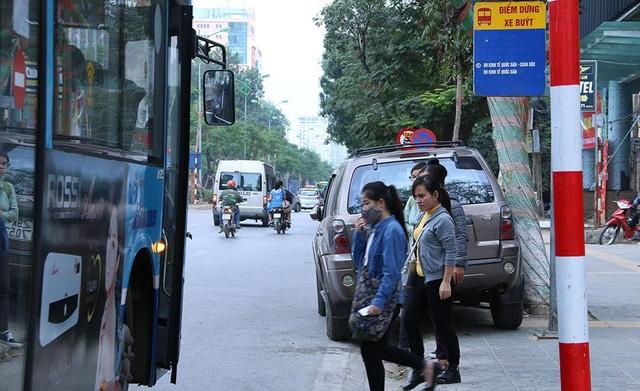 Chiếc ô tô màu xám ngang nhiên dừng đỗ ngay điểm đón - trả khác c xe buýt thường. Biển cấm dừng đỗ ngay phía trước chiếc ô tô này.