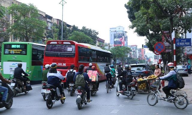 Ô tô ngang nhiên đỗ phép và người bán hàng rong chiến một làn đường, khiến các phương tiện khác đi lại rất khó khăn.