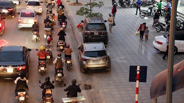 """Chiếc ô tô màu xám đỗ trên phố Giảng Võ, một hàng bánh xe trên vỉa hè, một hàng bánh xe dưới đường. Đây là cách đô xe """"lách luật mà các tài xế hay áp dụng."""