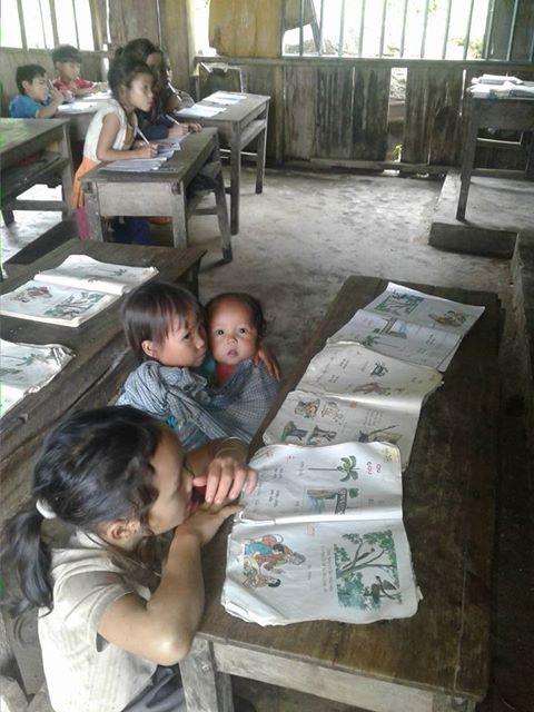 Bức ảnh em Hồ Thị Nhung địu em 8 tháng tuổi đến lớp học làm lay động dân mạng (ảnh Trần Tuấn)