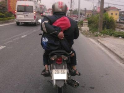 Người cha vừa lái xe máy vừa ôm con ngủ trên đường quốc lộ gây hoảng hốt