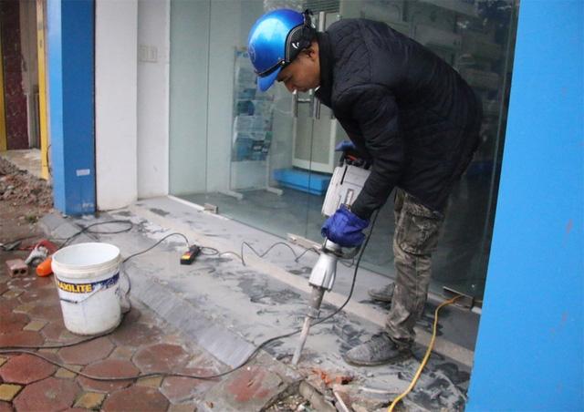 Lực lượng chức năng sáng nay tiếp tục dùng máy khoan bê tông để phá các bục bê tông lấn chiếm vỉa hè, lòng đường tại tuyến phố Tôn Đức Thắng (Đống Đa, Hà Nội).