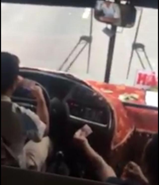 Tài xế và phụ xe soi số serie ăn tiền khi đang lái xe. (Ảnh cắt từ video clip)