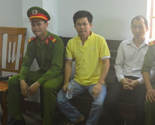 Bị cáo Trần Minh Lợi (áo vàng) trong lúc chờ phiên tòa xét xử