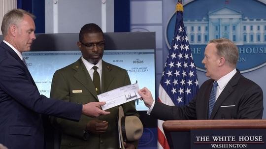 Phát ngôn viên Nhà Trắng Sean Spicer (phải) hôm 3-4 trao tấm séc trị giá 78.333 USD cho Bộ trưởng Bộ Nội vụ Ryan Zinke. Ảnh: AP