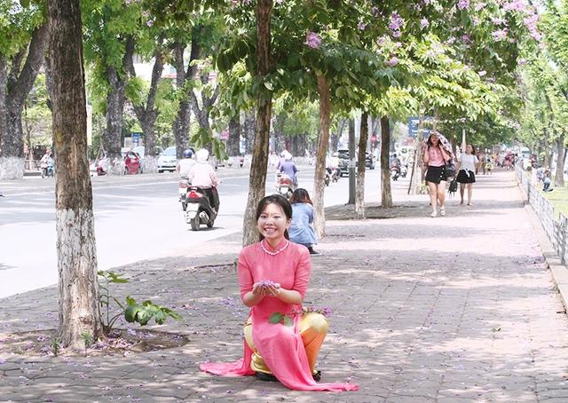 Nụ cười tươi tắn của thiếu nữ khi nhặt những cánh hoa màu tím rơi trên thềm phố