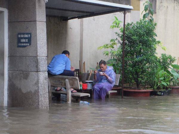 Chùm ảnh: Người Hà Nội mặc áo mưa ăn trưa giữa đường phố ngập lênh láng