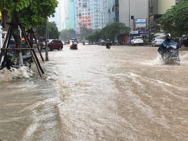 Chùm ảnh: Người Hà Nội mặc áo mưa ăn trưa giữa đường phố ngập lênh láng - Ảnh 1.