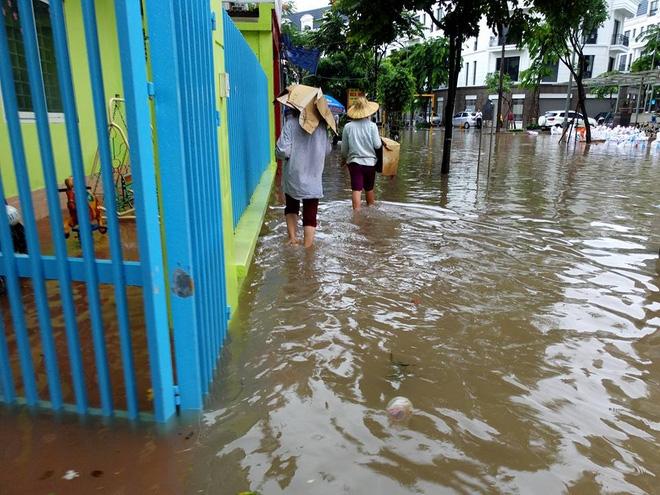 Chùm ảnh: Người Hà Nội mặc áo mưa ăn trưa giữa đường phố ngập lênh láng - Ảnh 8.