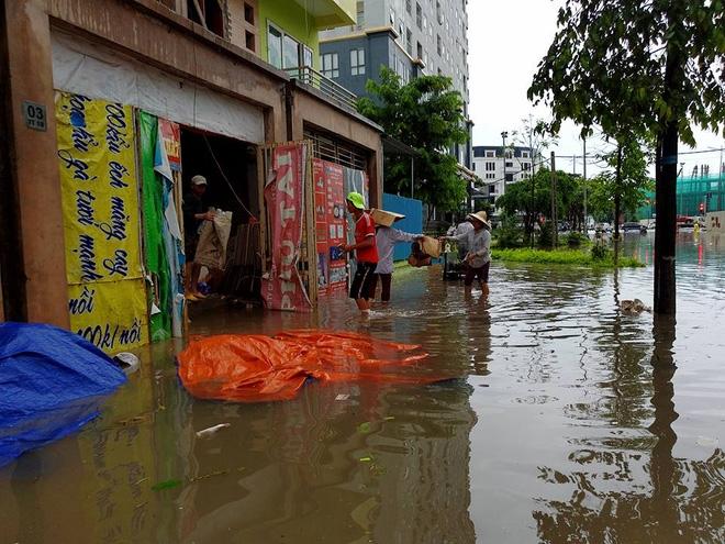 Chùm ảnh: Người Hà Nội mặc áo mưa ăn trưa giữa đường phố ngập lênh láng - Ảnh 9.