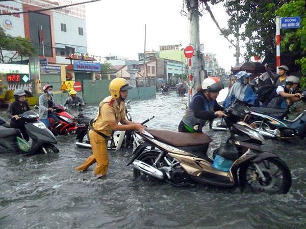 Một CSGT đẩy xe giúp người dân qua đoạn đường ngập nước (Ảnh: CAND).