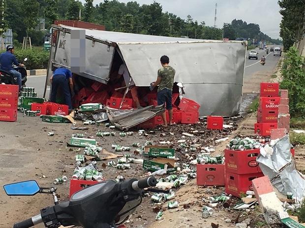 Bình Dương: Xe tải cày nát thành cầu rồi lật ngang đường, người dân đến thu gom bia giúp tài xế - 1