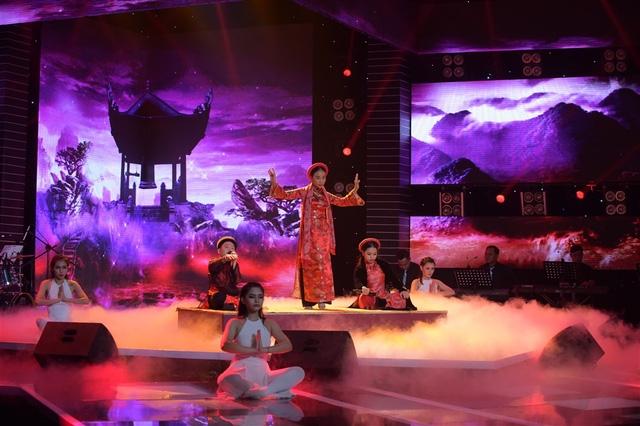 """Ca sĩ Đoan Trang vẫn đầy bản lĩnh khi """"giả vờ"""" đứng lên múa, nhưng thực chất là để tìm lại micro."""