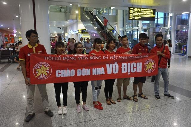 Tại khu A2 sân bay Nội Bài, một nhóm người hâm mộ đã có mặt từ rất sớm chuẩn bị hoa và khẩu hiệu để chào đón các cô gái tuyển bóng đá nữ Việt Nam.