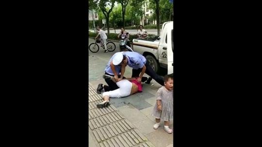 Trung Quốc: Cảnh sát quật ngã người phụ nữ đang đang bế trẻ - Ảnh 5.