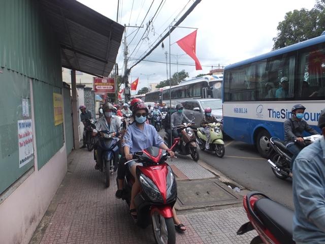 Kẹt xe kéo dài khiến nhiều người đi xe máy chạy lên vỉa hè mong thoát thân.