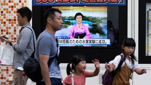 Người dân Nhật Bản đi qua một màn hình chiếu bản tin về vụ thử hạt nhân lần 6 của Triều Tiên ngày 3/9 ở Tokyo (Ảnh: CNBC)