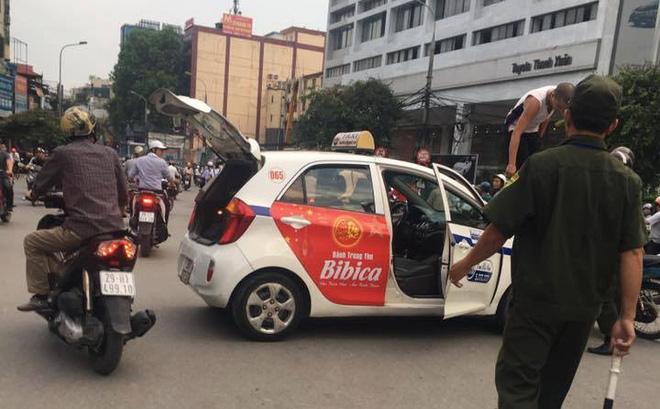 Bị nhắc nhở đi vào đường cấm, tài xế taxi trèo lên nóc xe ăn vạ