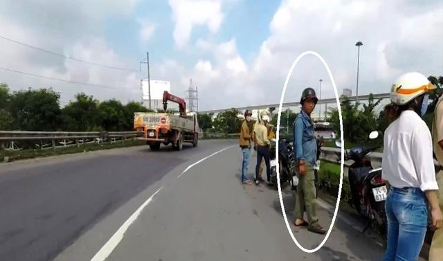 Người đàn ông đứng gần hiện trường khi tổ công tác của CSGT Đội Rạch Chiếc đang xử lý người vi phạm trên cầu vượt Thủ Đức.