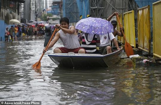 Bão vừa đổ bộ, người dân Philippines ngụp lặn trong nước lũ - Ảnh 2.