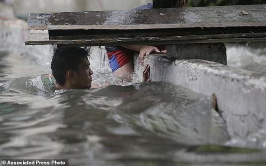 Bão vừa đổ bộ, người dân Philippines ngụp lặn trong nước lũ - Ảnh 10.