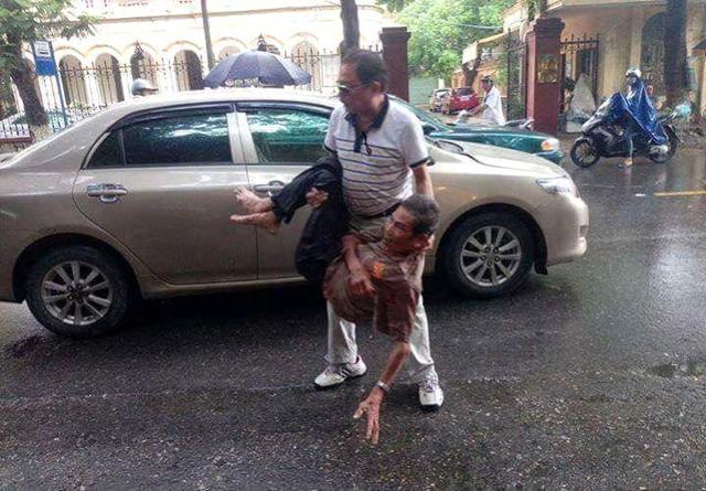 Hình ảnh tài xế ô tô bế ông cụ vào lề đường kiếm tra rồi cho đi bệnh viện. Ảnh: (Bạn đọc cung cấp)