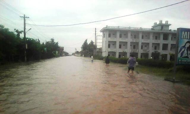 Nước biển dâng cao gây ngập lụt khiến người dân đi lại vô cùng khó khăn (ảnh: Phùng Thành)