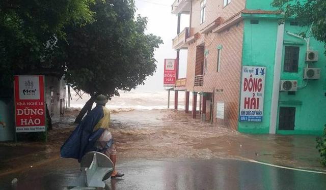 Tại thị trấn Thịnh Long nước biển tràn qua bao đê ngoài vào trong (ảnh: Phạm Tùng)