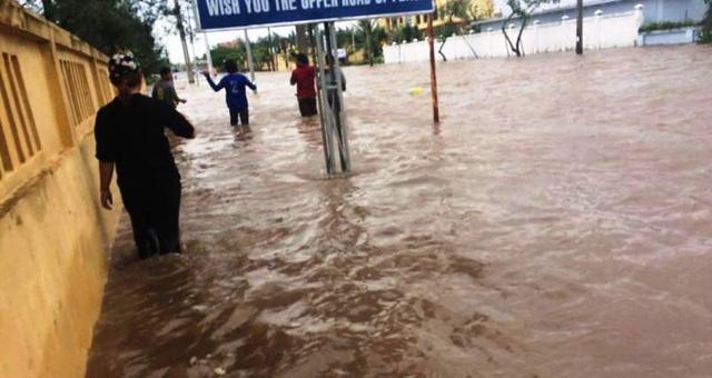 Người dân bì bõm lội nước trên các tuyến đường bị ngập (ảnh: Phạm Tùng)