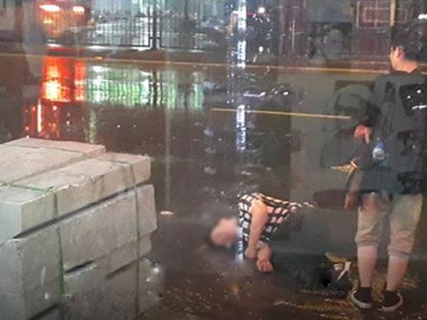 Bất chấp mưa bão, chàng trai vẫn nằm lăn ra đường giả vờ ngất để