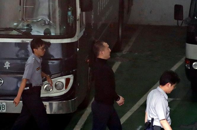 Cựu sinh viên Trung Quốc  Chu Hoàng Húc (giữa) sau khi bị tuyên án ngày 15.9 /// Reuters