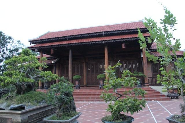 Căn nhà rường gỗ được xây dựng trong khuôn viên vườn, xung quanh bao bởi tường bê tông, có cây cối