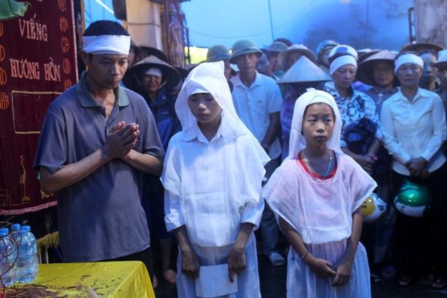 Thì chồng nạn nhân và 2 con nhỏ đứng lặng mình bên bàn thờ