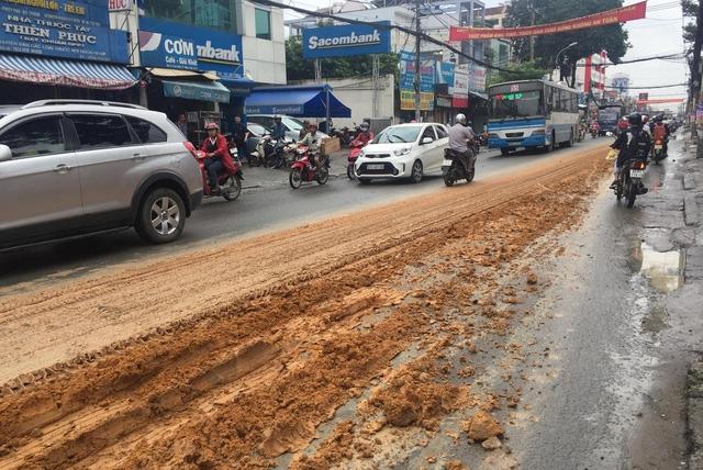 Hàng tấn đất đỏ đổ tràn trên đường Lê Văn Việt, quận 9, TPHCM từ chiếc xe ben không che chắn.