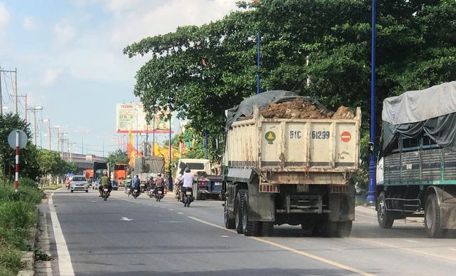 Xe chở đất chạy đầy trên đường. Đất đá chở trên xe không được che chắn cẩn thận.