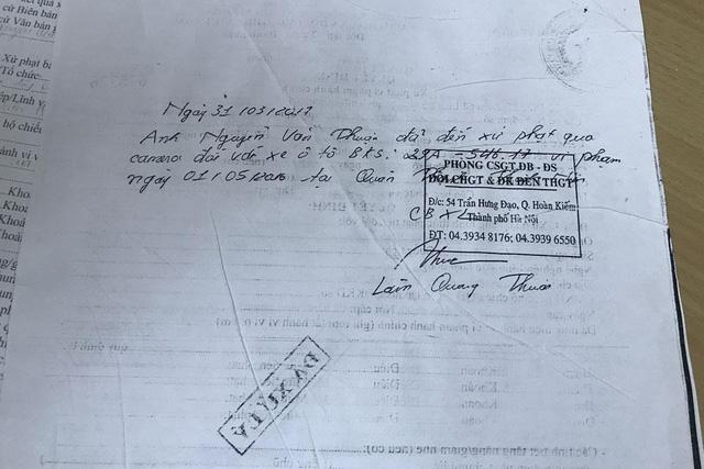 Một biên lai kèm thông báo viết tay về việc một chủ xe đã nộp phạt nguội mà Trung tâm Đăng kiểm lưu giữ.