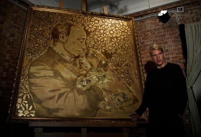Họa sĩ Alexey Sergienko bên tác phẩm The Golden Putin (Ảnh: Newsweek)