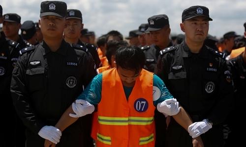 Cảnh sát Trung Quốc áp giải một nghi phạm lên máy bay ở sân bay Phnom Penh, Campuchia, ngày 12/10. Ảnh: Reuters.
