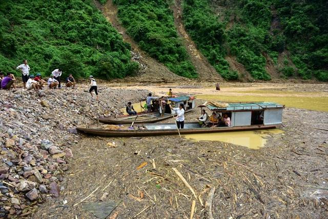 Gỗ trên thượng nguồn bị lũ cuốn theo, ngập kín một đoạn sông. Nhiều nơi, người dân tụ tập trên bờ để đợi tin tức từ thuyền đi tìm kiếm người mất tích.