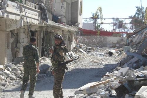 SDF đứng trên đường phố đổ nát ở Raqqa. Ảnh: AP.